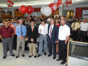 Gary Schoch, center with white shirt & pink tie, surrounded by Toyota and Koons staff in celebration of his new vehicle.